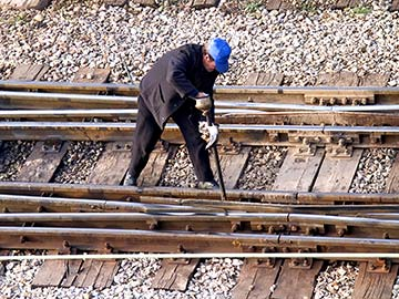 This rail worker faces many dangers every day. If you have been injured while working for a railroad company, call a Bay City FELA attorney now.